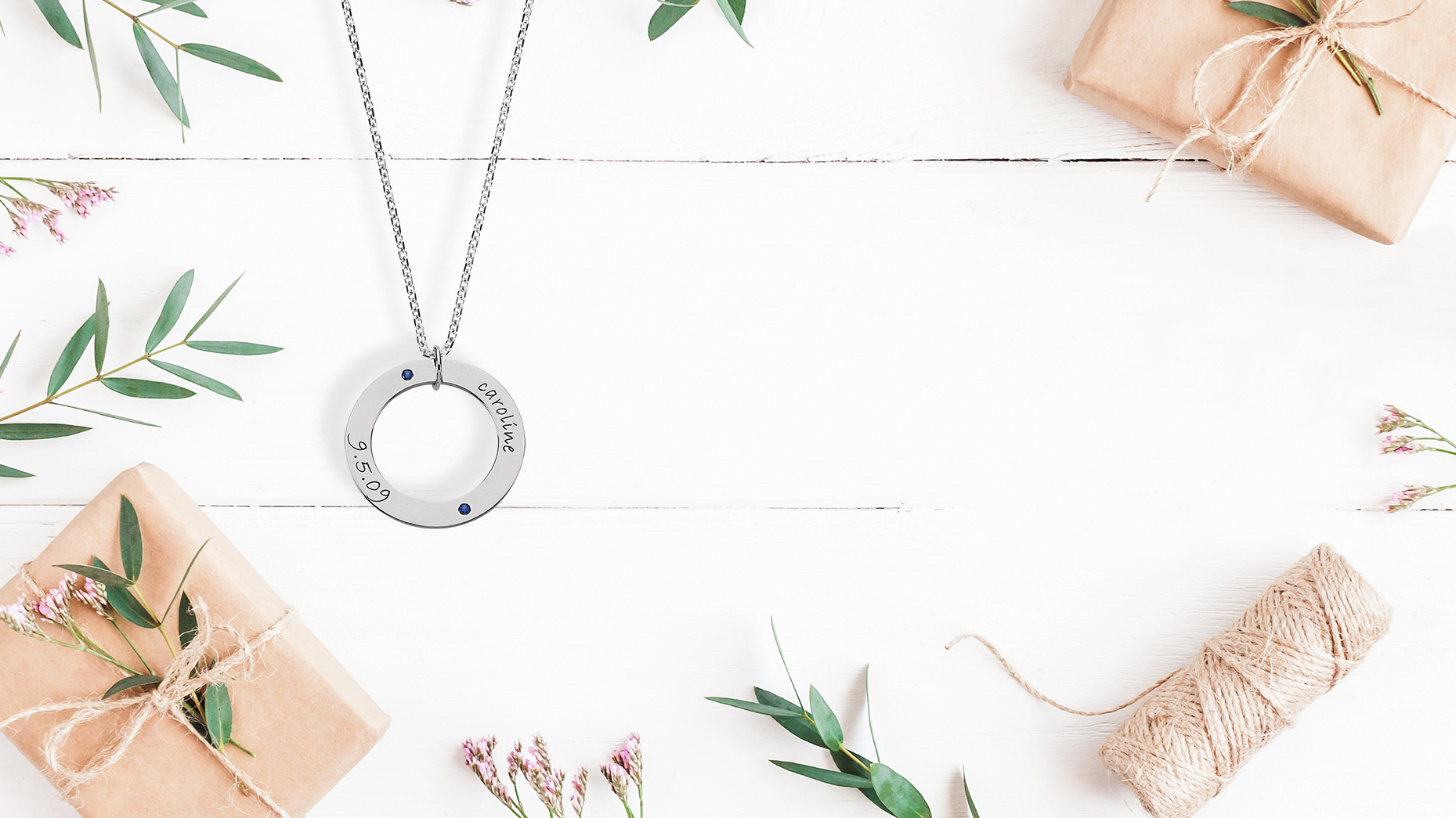 Family necklace on white backdrop with flowers